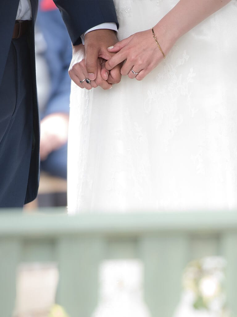 Bride and groom holding hands during their wedding ceremony