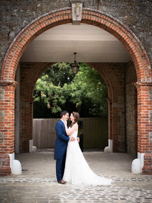 Bride and groom in arch at wedding venue in Kent