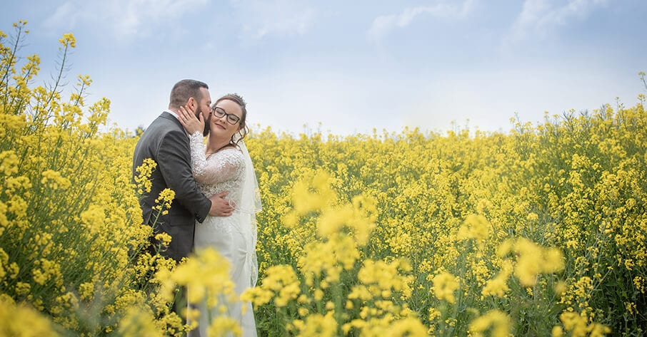 Newlywed kiss in field of flowers
