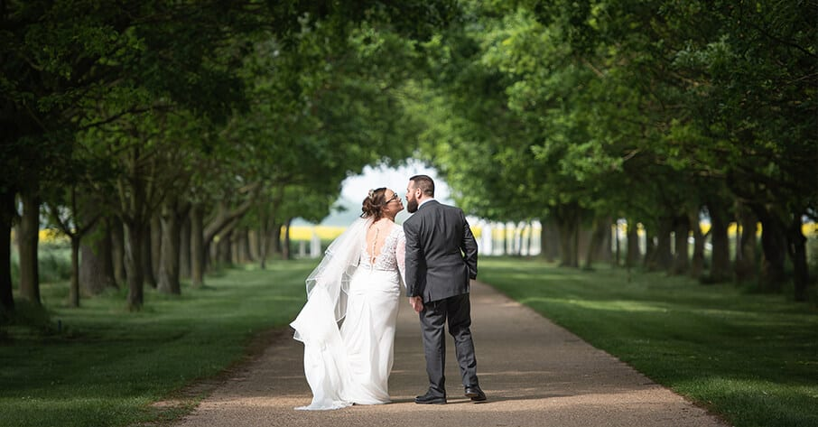 Newlyweds framed by tree lined drive.